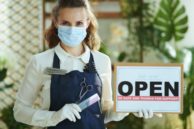elegant small business owner woman in apron showing open sign